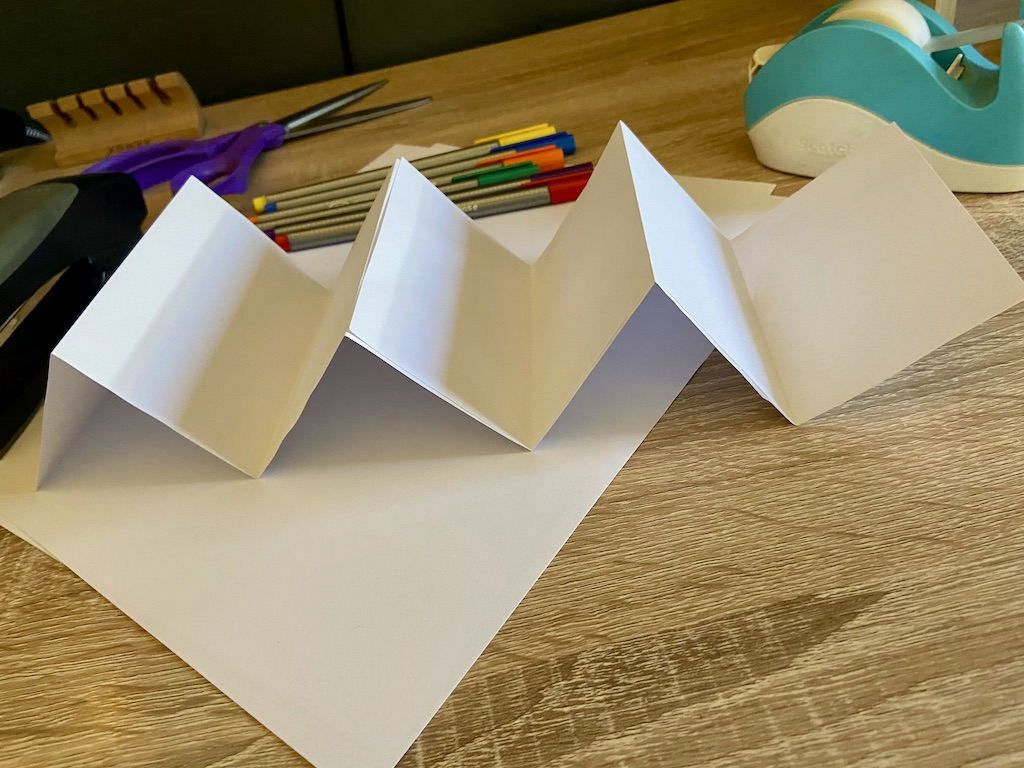 Glue your Ws together to make an accordion (or use tape if you don't have glue). If you are using a thick type of paper, you might want to use a heavy object like a book to press down on top of it for a few minutes.