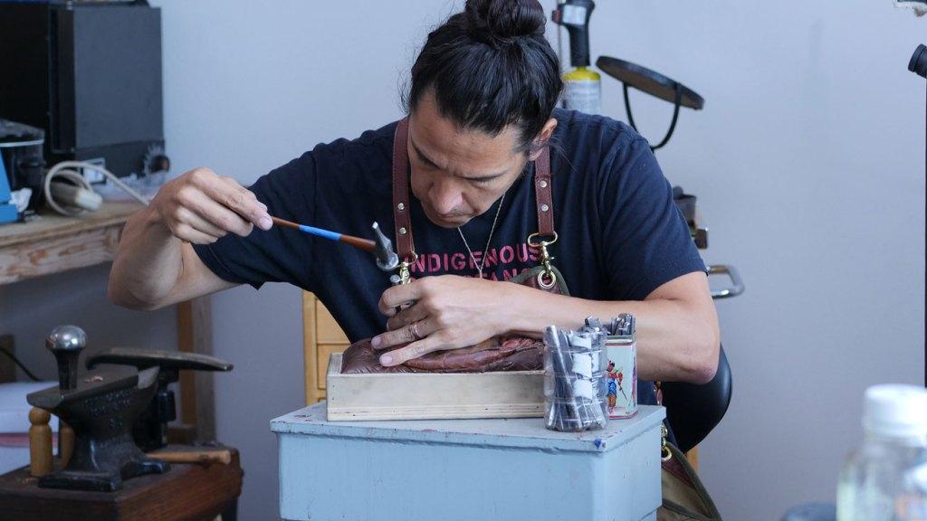 Artist Nicholas Galanin chasing a copper mask. Craft in America STORYTELLERS