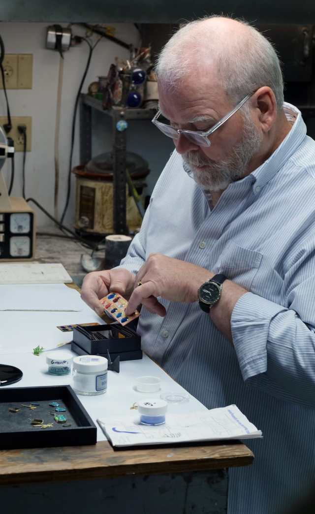 Tom Herman shows enamel samples. Denise Kang photo. JEWELRY episode of Craft in America