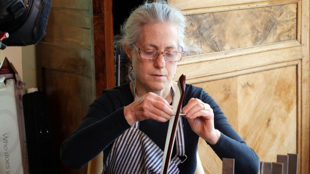 Bowmaker Susan Lipkins rehairs a bow. Denise Kang photo. HARMONY episode of Craft in America
