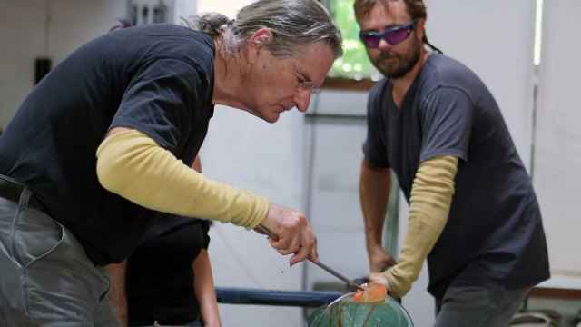 Glass artist Richard Jolley shapes glass with lead assistant James A. Breed. Denise Kang photo. HARMONY episode of Craft in America