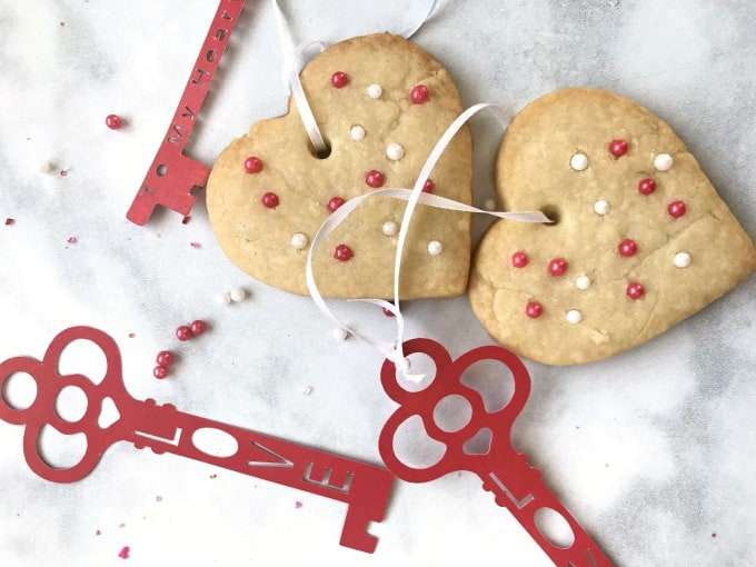 two Perfect Valentines Heart Shortbread Cookies on a white counter with a red key tag that says love, the cookies have red and white sprinkles.