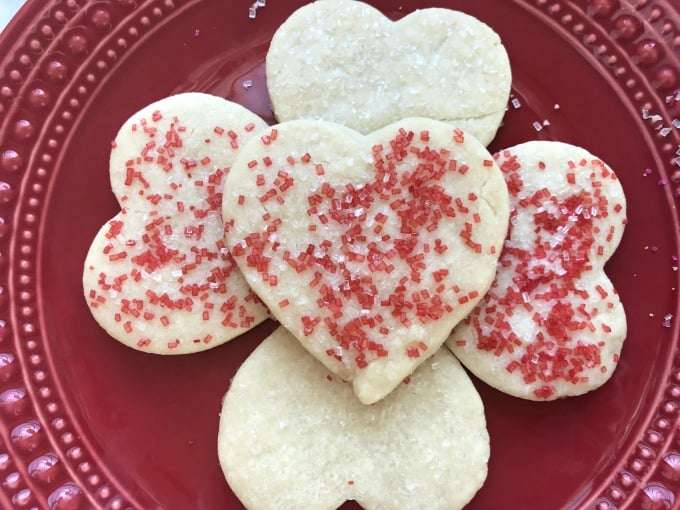 five Perfect Valentines Heart Shortbread Cookies on a dark red plate with red and whit sprinkles