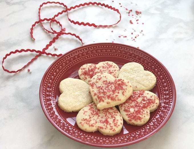 heart shaped Shortbread cookies on a red plate with a red rick rack ribbon