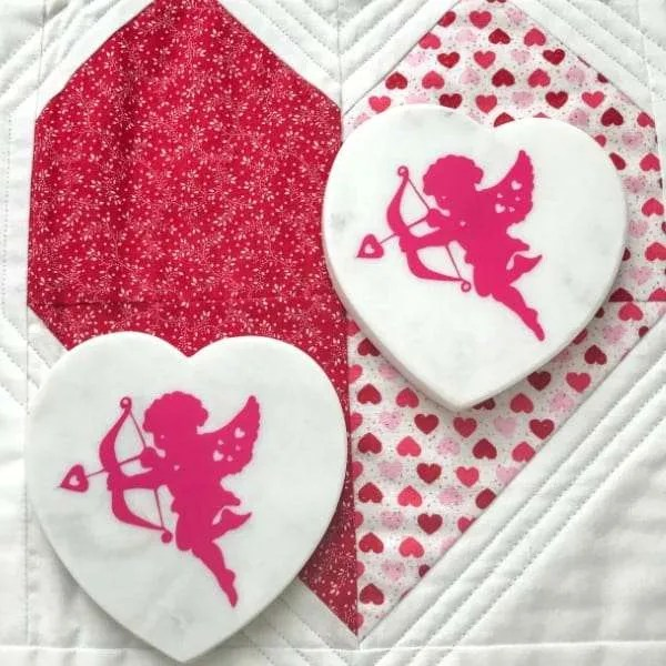 Valentines DIY Vinyl Coasters white heart shaped marble coaster with red cherub vinyl decal on red and white quilted table runner