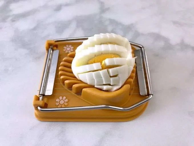 hard boiled egg in egg cutter on white counter