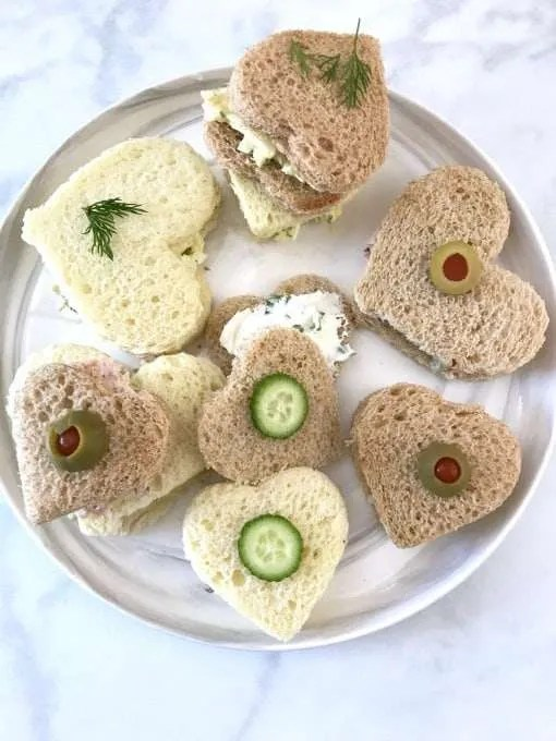 Valentines Party Tea Sandwiches heart shaped bread with olive, dill and cucumbers on top on a white plate on a white counter