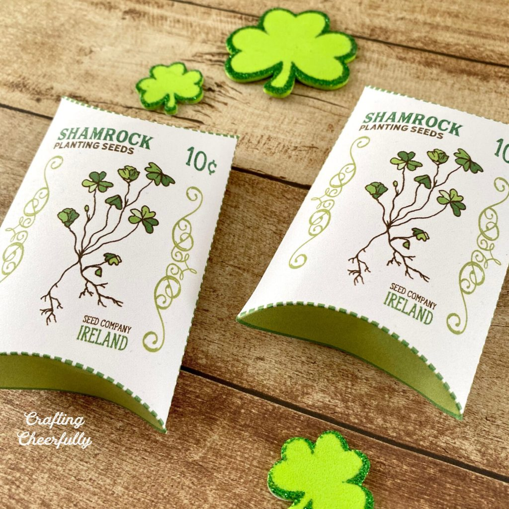 """St. Patrick's Day pillow box treat boxes lay on a wooden table with little green shamrocks around them. The boxes have a picture of a shamrock plant on them with the words """"Shamrock Planting Seeds"""" on them."""