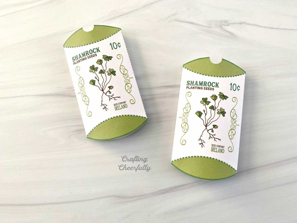 Two shamrock treat boxes lay on a table. They are adhered on the left side.