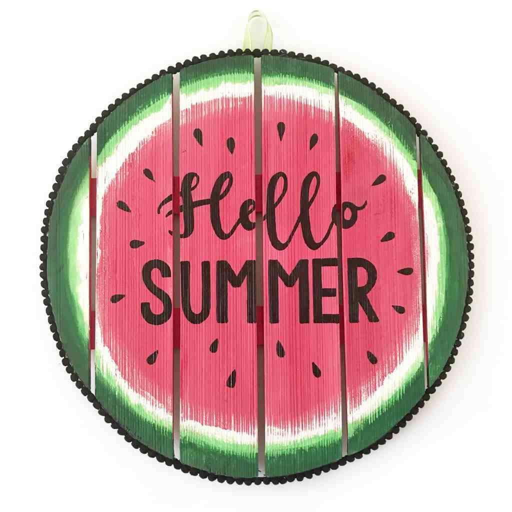 "Circular watermelon wooden sign with the words ""Hello Summer"" on it."