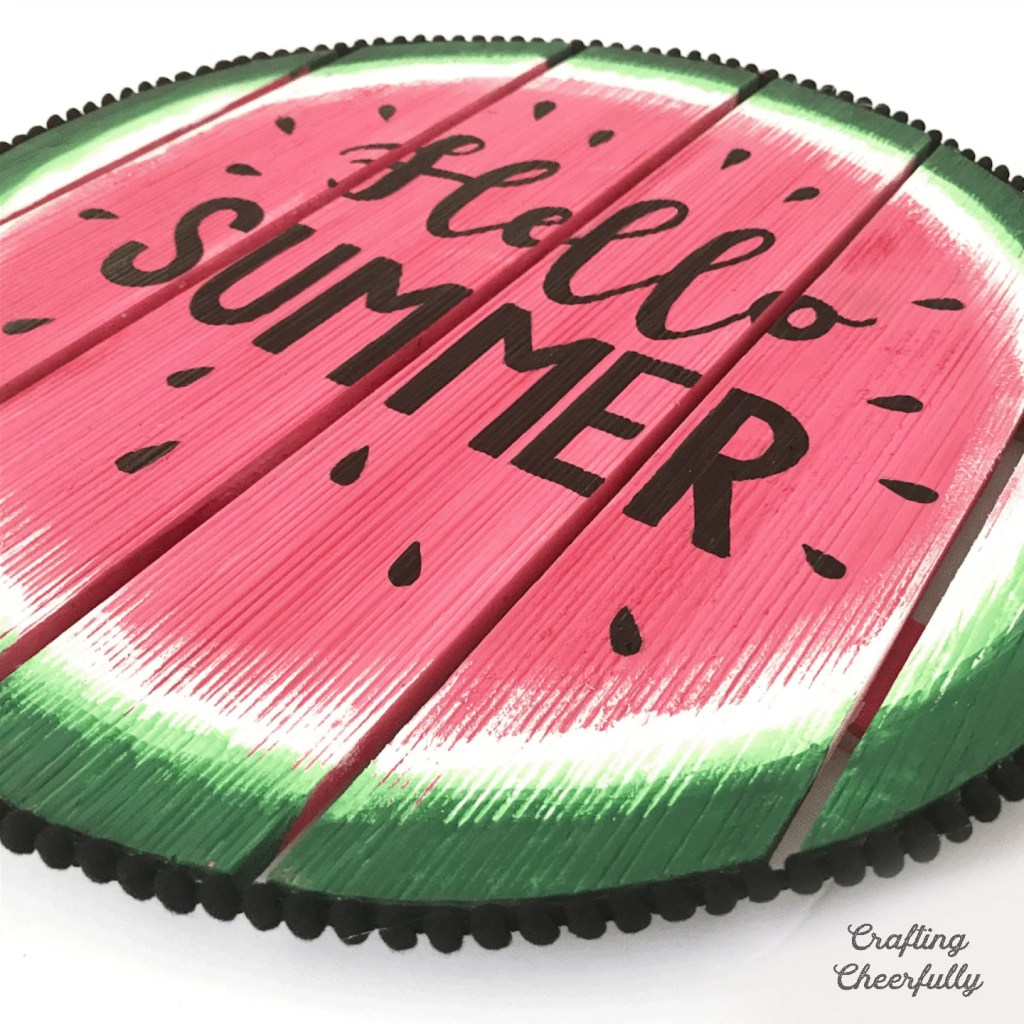 "Close up shot of Circular watermelon wooden sign with the words ""Hello Summer"" on it."