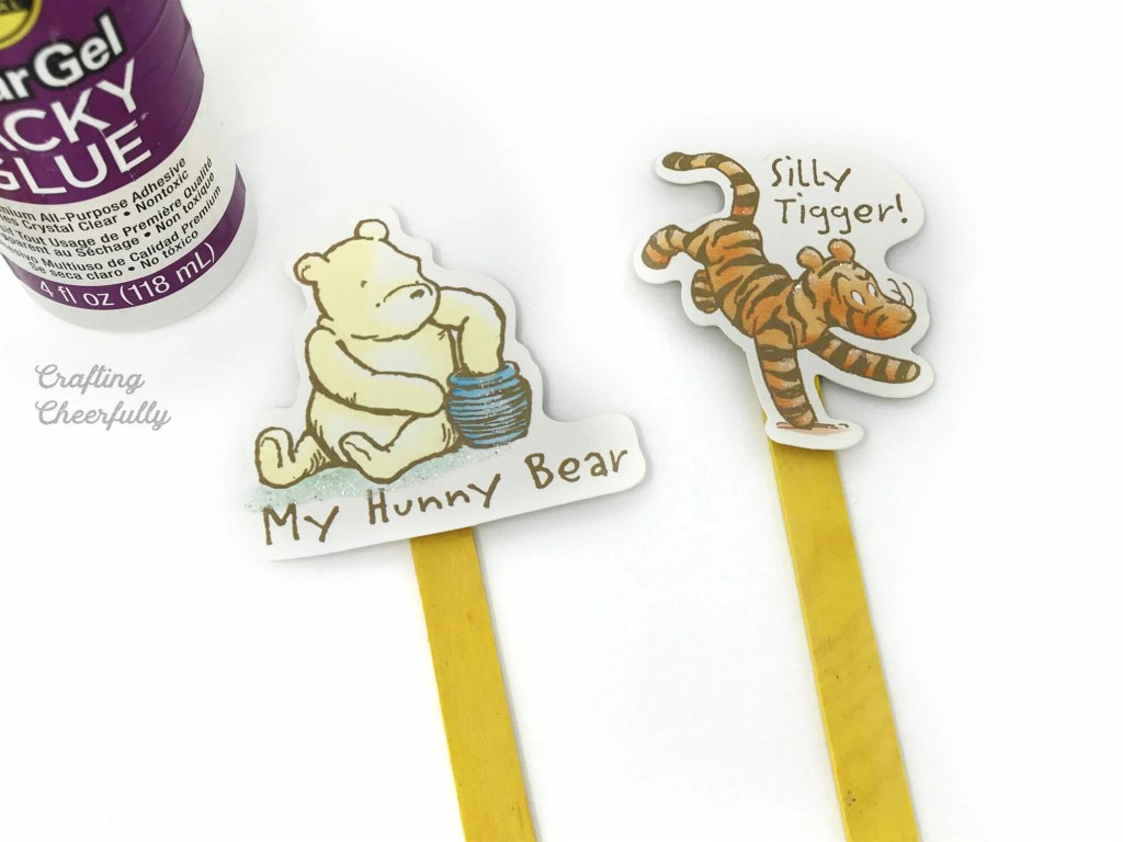 Winnie the Pooh paper embelishments glued to the top of yellow popsicle sticks.