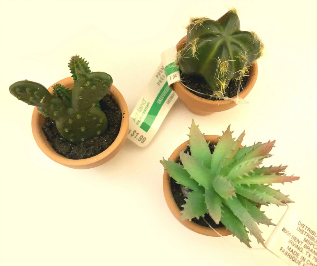 Overhead picture of three small fake cactus plants.