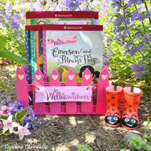 Pink fence book box outside in garden holding Wellie Wisher books. A pair of ladybug wellies sit next to it.