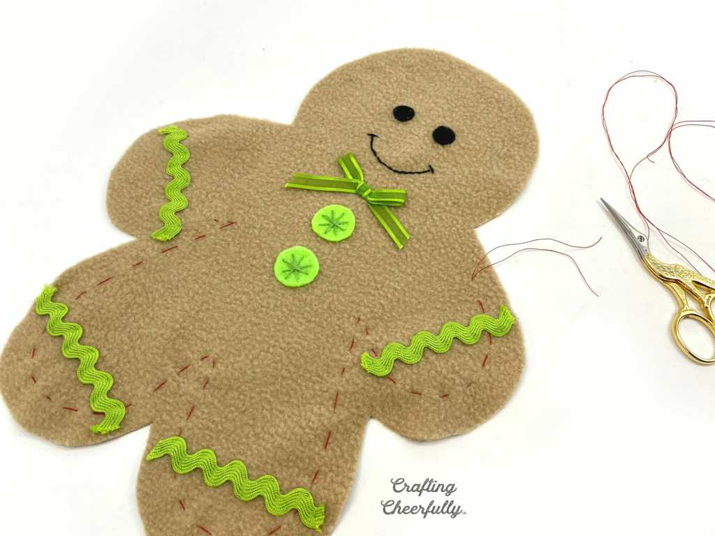 Fleece gingerbread boy laying on a white table. Red tracing threads being removed.