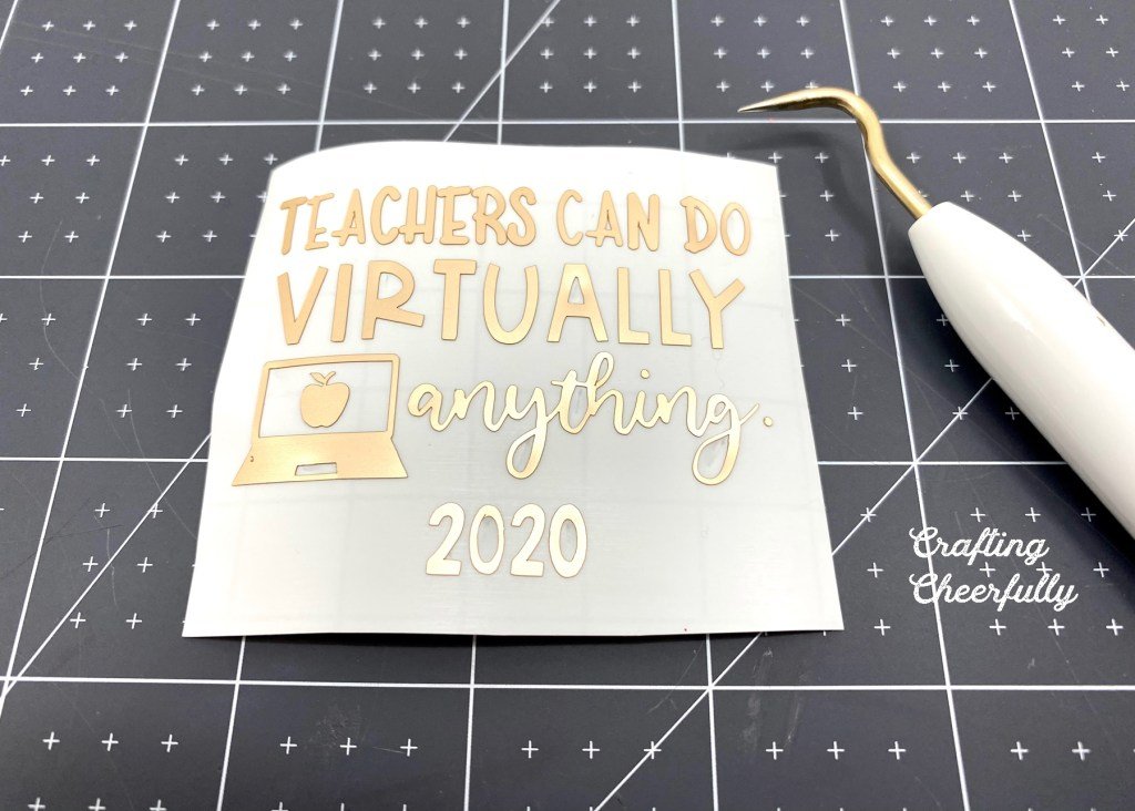 """Adhesive foil cut in the words """"Teachers can do virtually anything 2020"""" laying on a black self-healing cutting mat next to a weeding tool."""