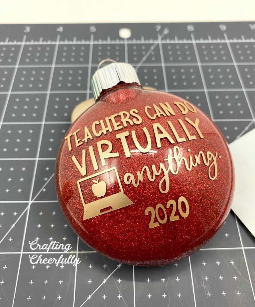 """Red ornament with gold adhesive vinyl added to it with the message """"Teachers can do virtually anything"""" and the date."""