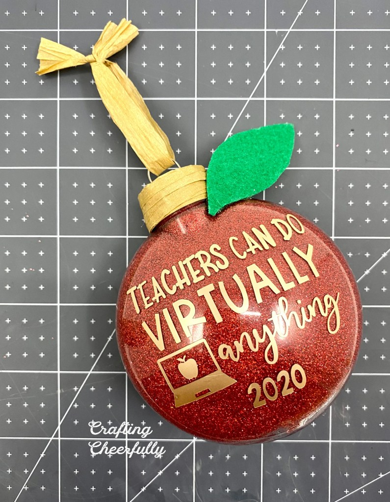 Red glitter ornament with brown raffia wrapped around the top of the ornament. A green felt leave at the top of it. Brown raffia hanging loop.