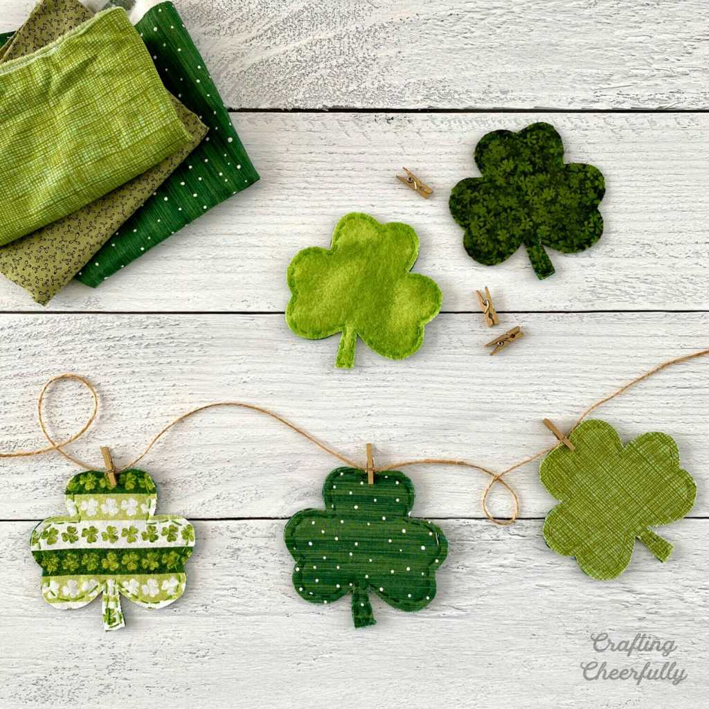 Shamrock banner made from scraps of green fabric lays on a white wooden table. Fabric scraps sit nearby.