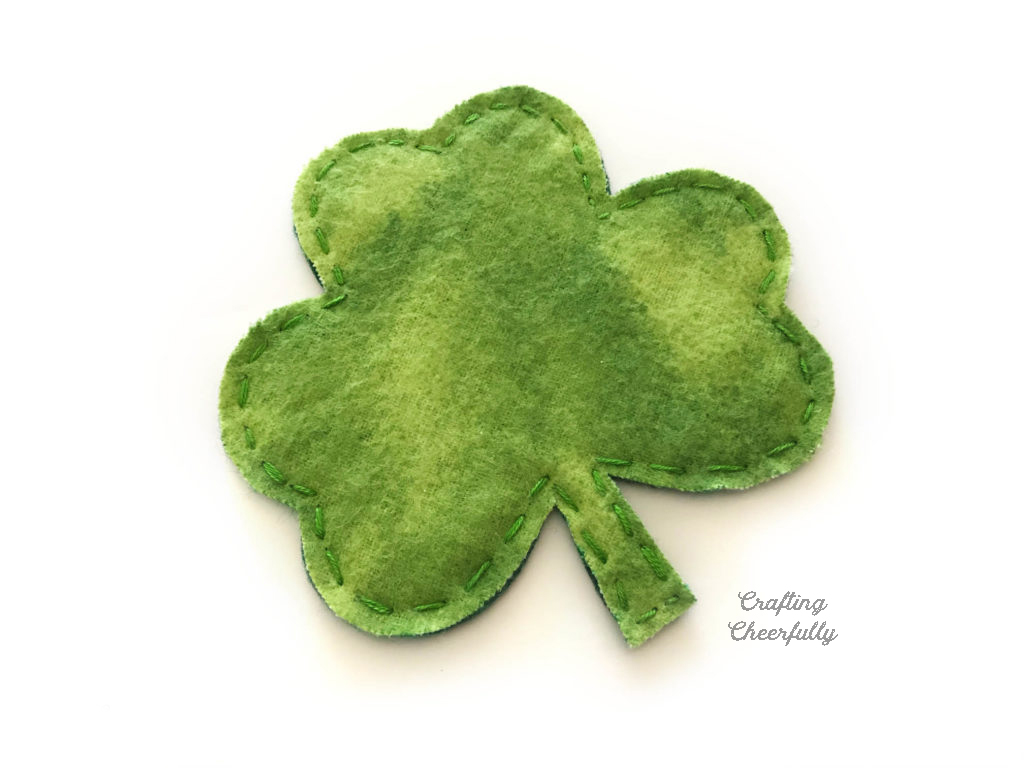 A green fabric shamrock with a small hand-embroidered running stitch around the edges.