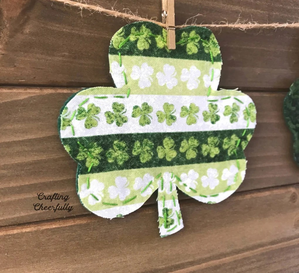 A fabric shamrock is hung on a piece of twine with a mini clothespin.