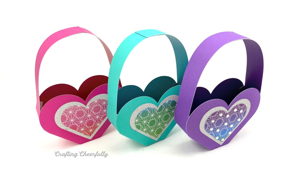 Three heart shaped Valentine boxes sit in a row on a white table. They are purple, teal and pink.