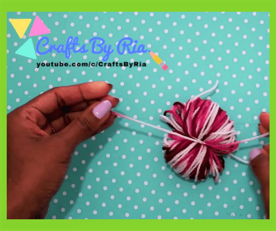 diy pom pom rug-steps-tie it using another piece of yarn
