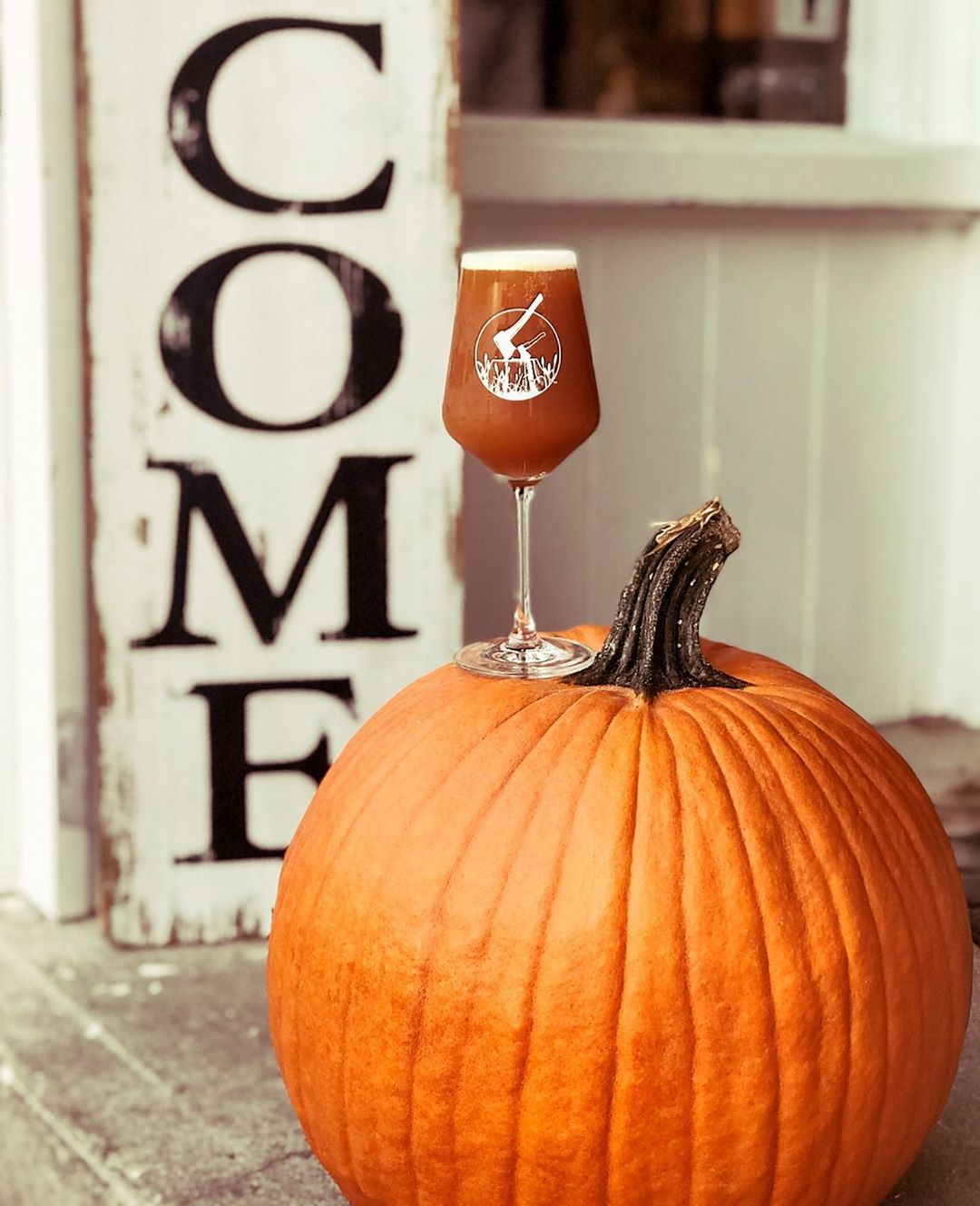 A Teku glass full of pumpkin IPA that is resting atop a large pumpkin on a porch.