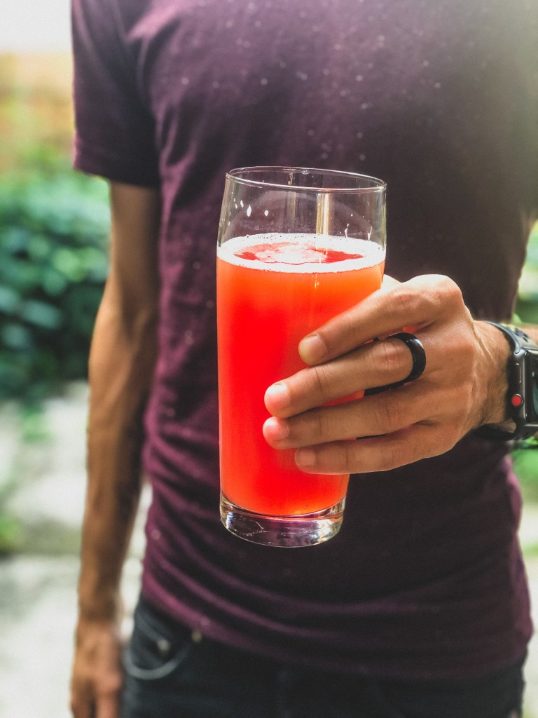 A man holding a glass of reddish/pink beer. (Pink Lemonade IPA by Untitled Art Brewing).