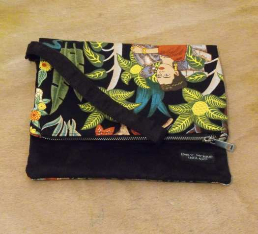 Emily McNair Design Frida Kalho black printed clutch with strap on a wooden table