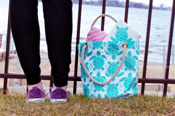 Aquamarine Sea Turtle Beachcomber bag next to woman wearing purple shoes