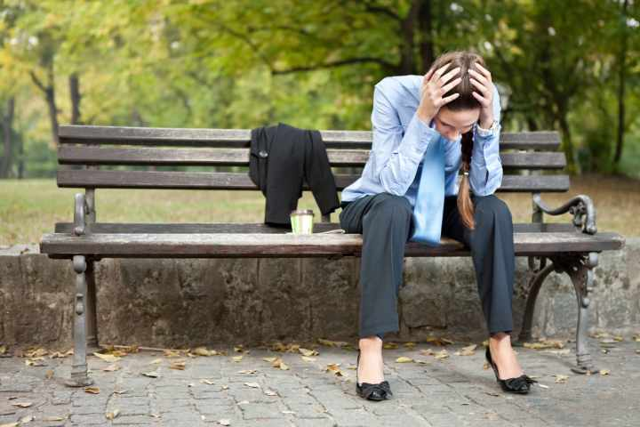 worried caucasian businesswoman sitting on bench in park