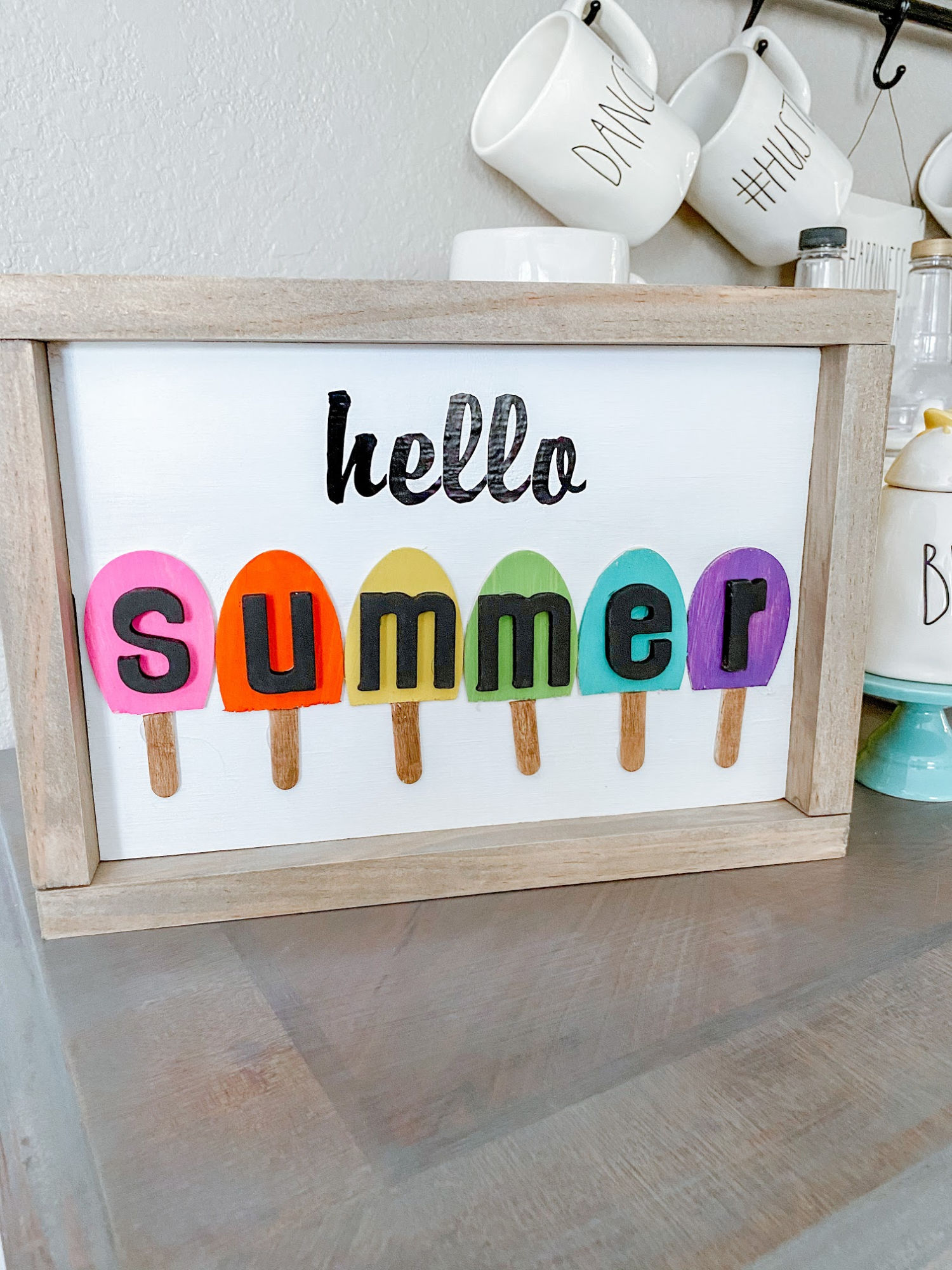 Create this cute DIY Hello Summer sign using paints, wood, and popsicle sticks. This project is both fun and easy to make for your home decor this summer. #summerdecor #homedecor #summer #diysign #woodsigns #diywoodsign
