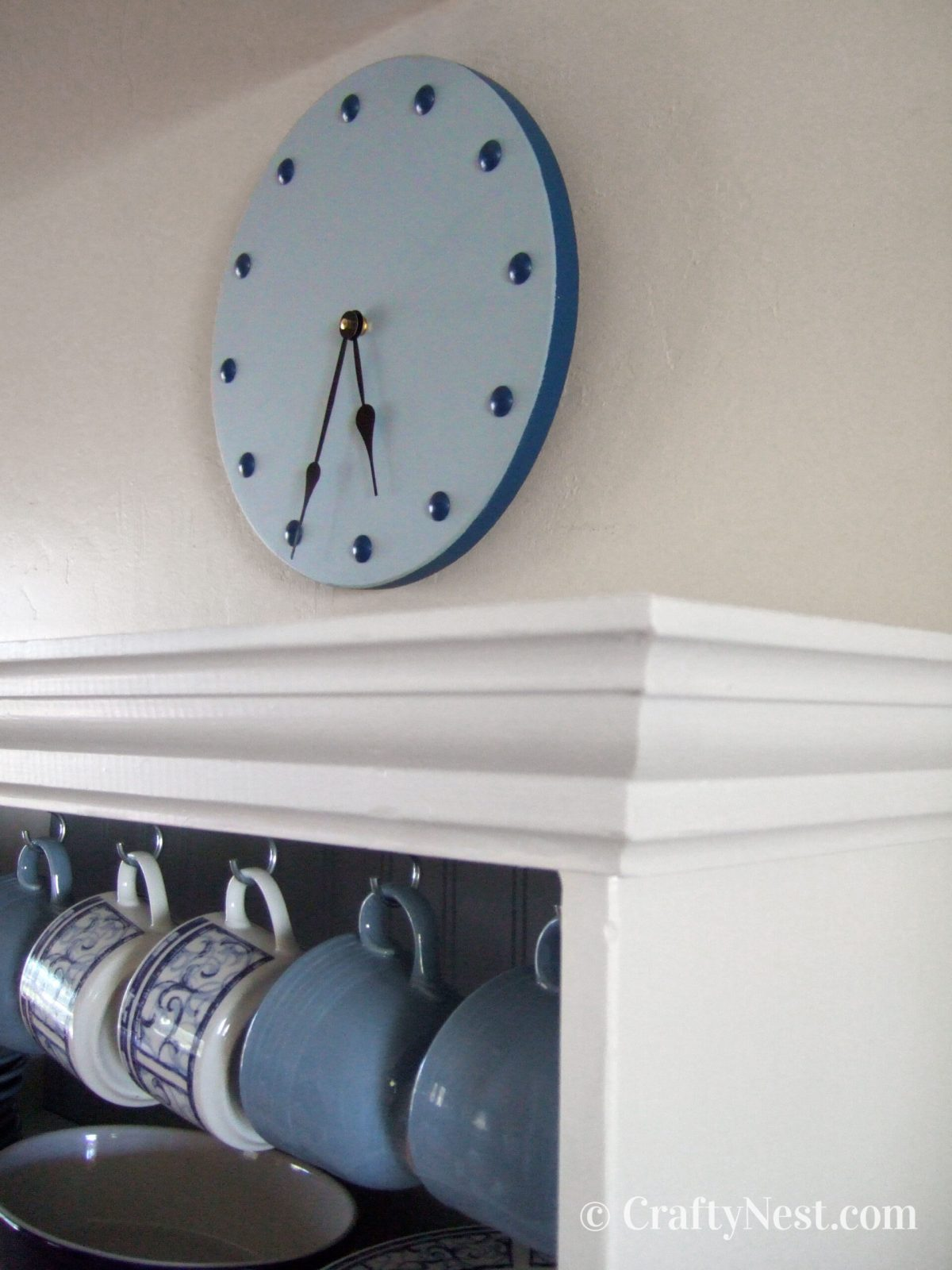 Blue wooden clock with furniture-nail numbers, photo