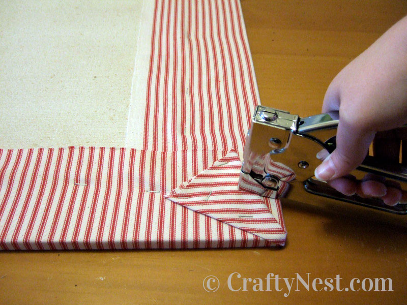 Stapling the fabric to the homasote board, photo