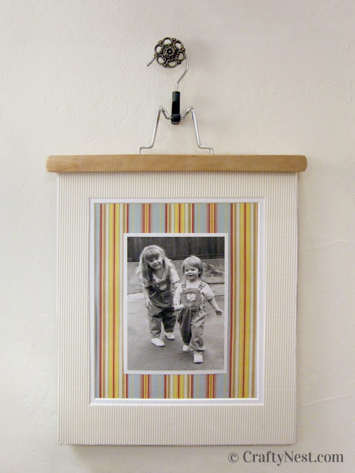 Photo framed with a mat, hanging from a pants hanger, photo