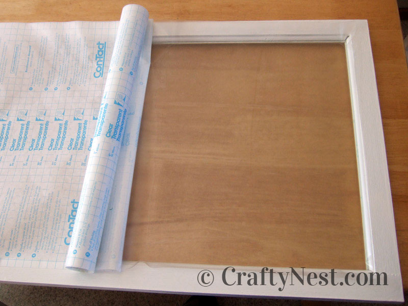Applying Con-Tact paper to the glass, photo