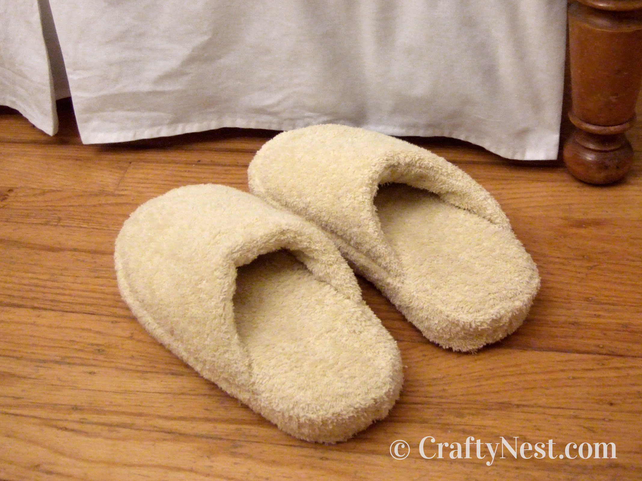 Handmade terrycloth slippers next to a bed, photo