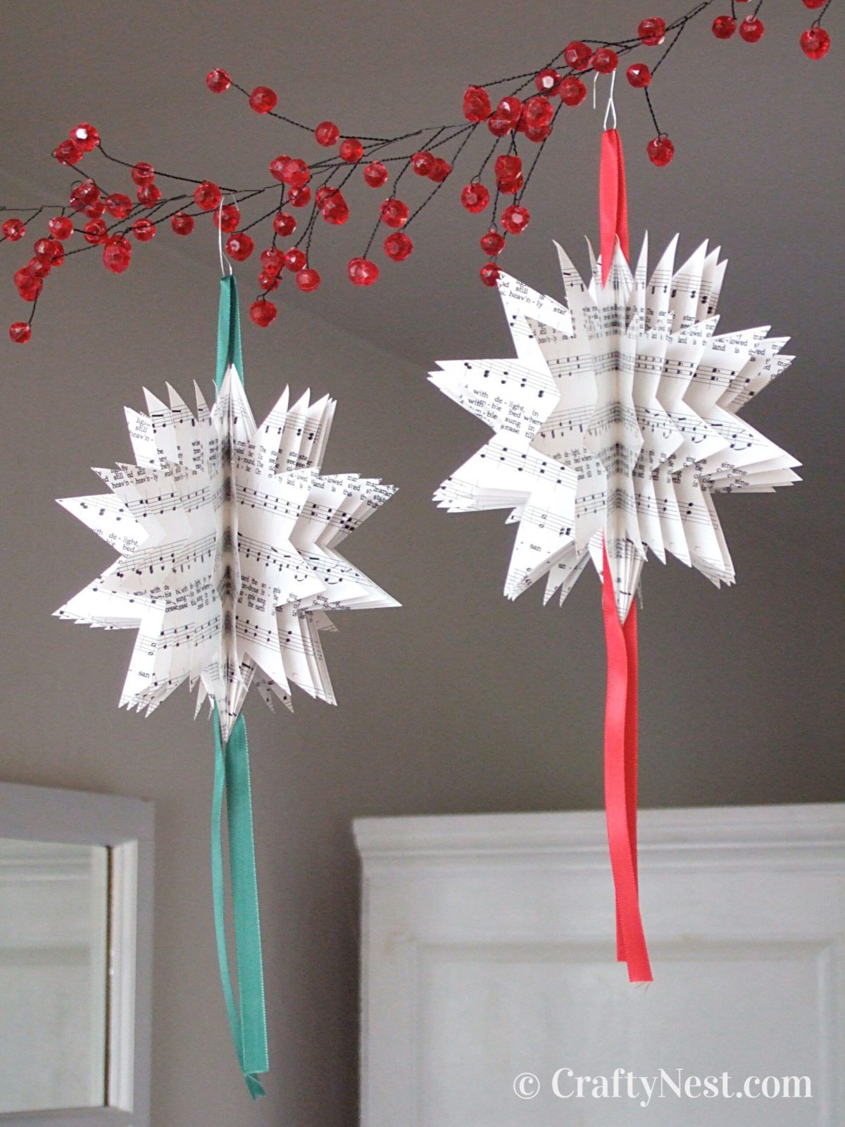 Two Christmas ornaments made with sheet music, photo