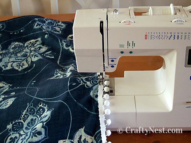Sew on the pom-pom trim, photo