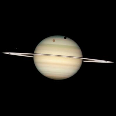 24 lutego 2009 roku Kosmiczny Teleskop Hubble'a zarejestrował niezwykłe ujęcie czterech księżyców Saturna przechodzących przez jego tarczę lub w pobliżu niej — w tym największego z nich, Tytana. Fot. NASA, ESA i Hubble Heritage Team (STScI/AURA)