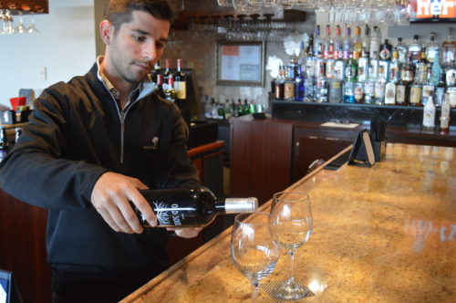 Joe Town, Moon Brook Country Club manager and certified sommelier, demonstrates how to pour a glass of wine.
