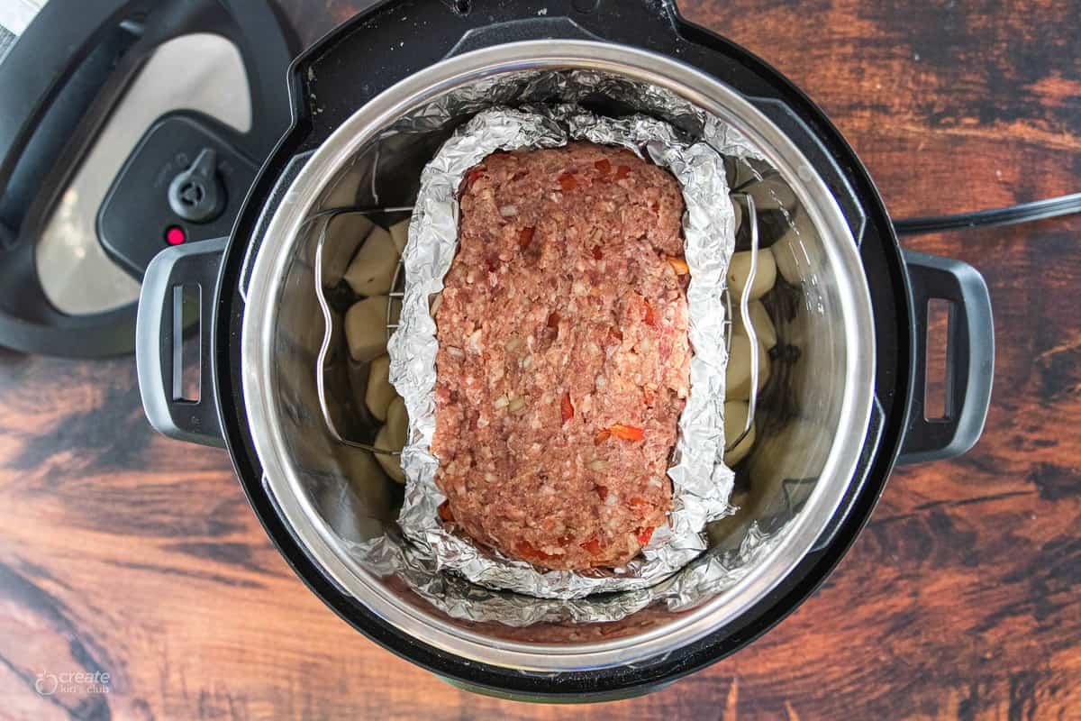 raw meatloaf on aluminum foil in instant pot