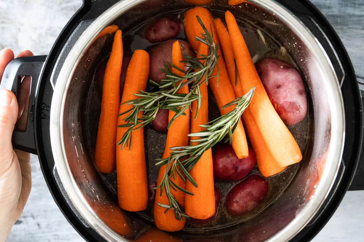 instant pot filled with herbs, raw vegetables and cooked roast