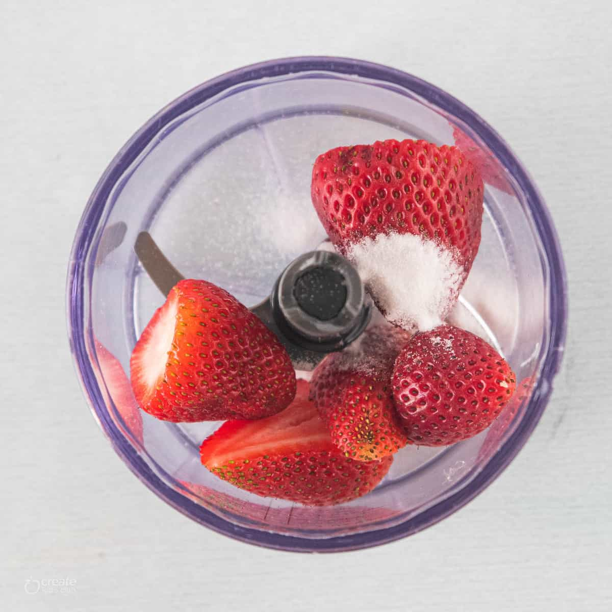 Strawberries and sugar in a blender.