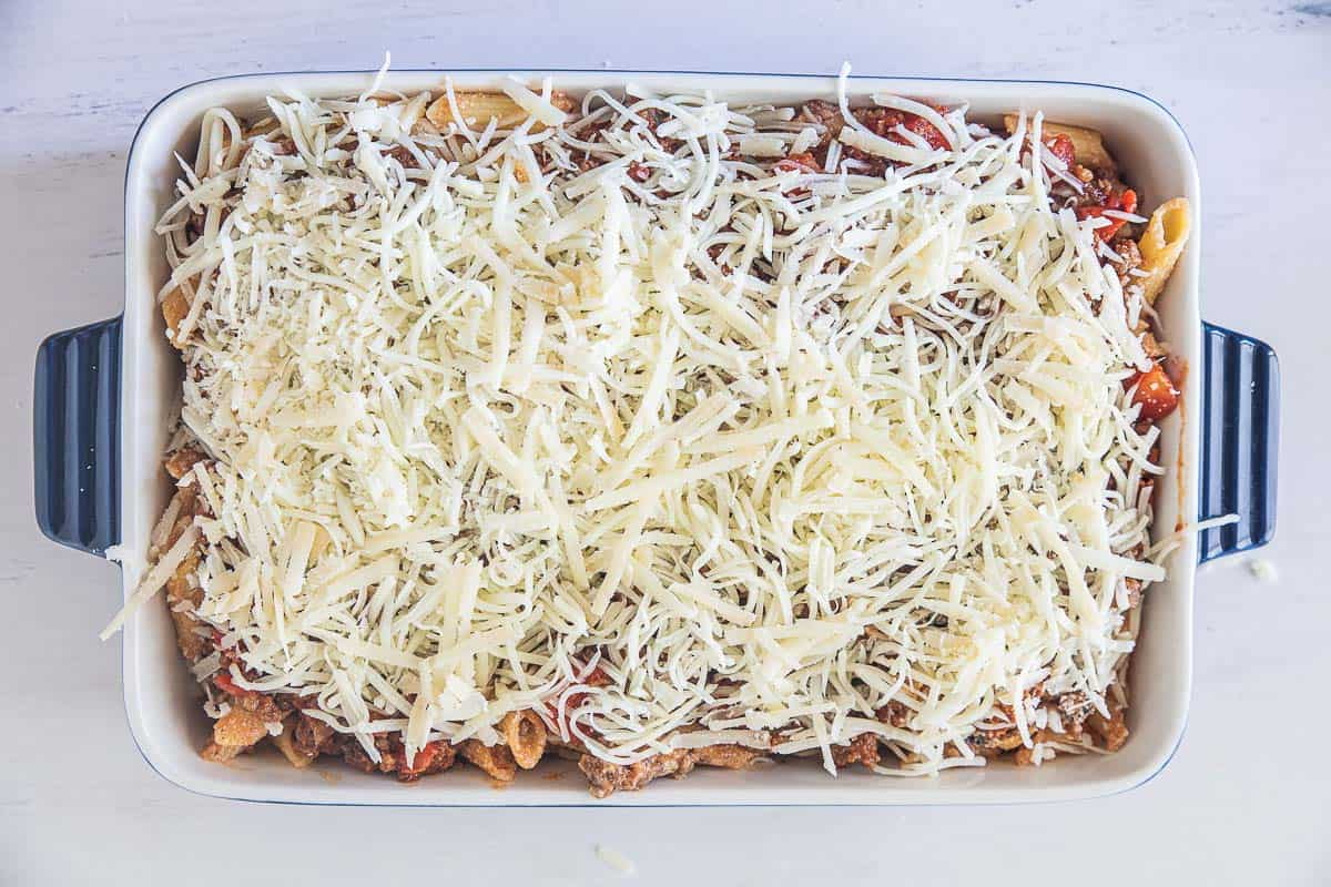 cheesy gluten free ziti with sausage in baking dish topped with cheese