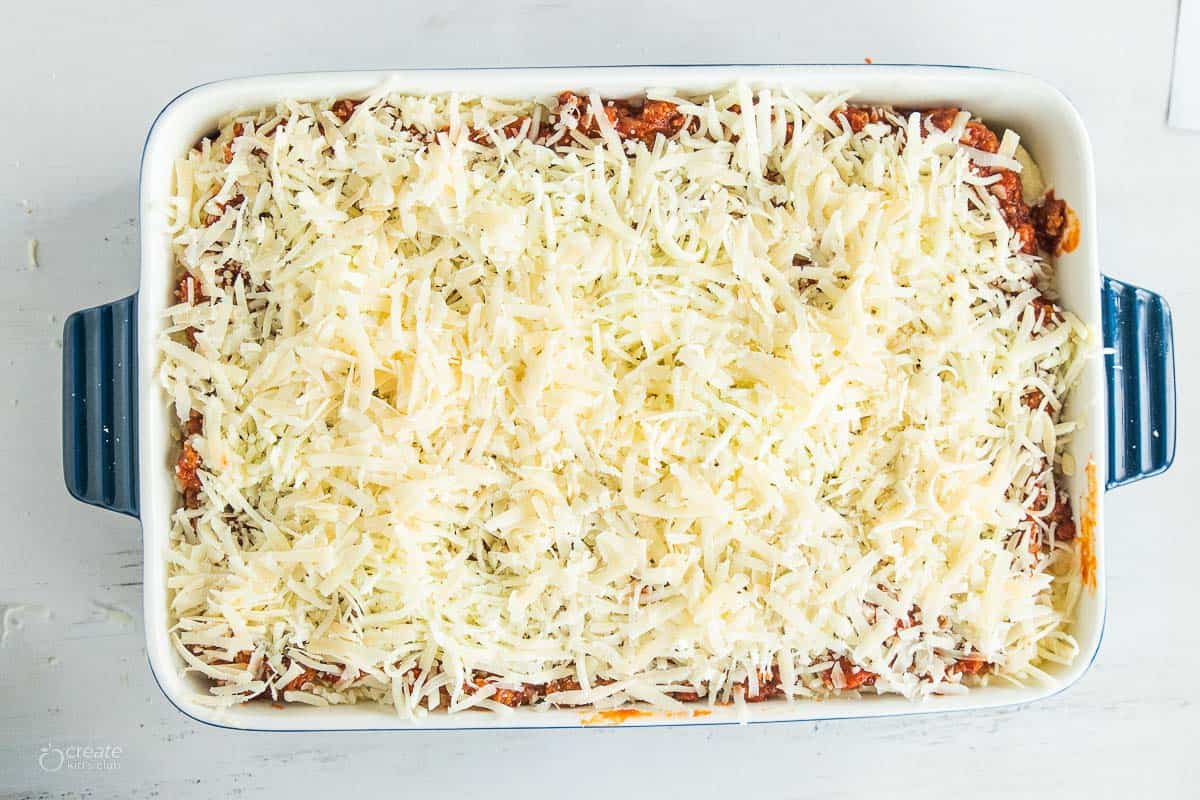 lasagna in baking dish topped with shredded cheese