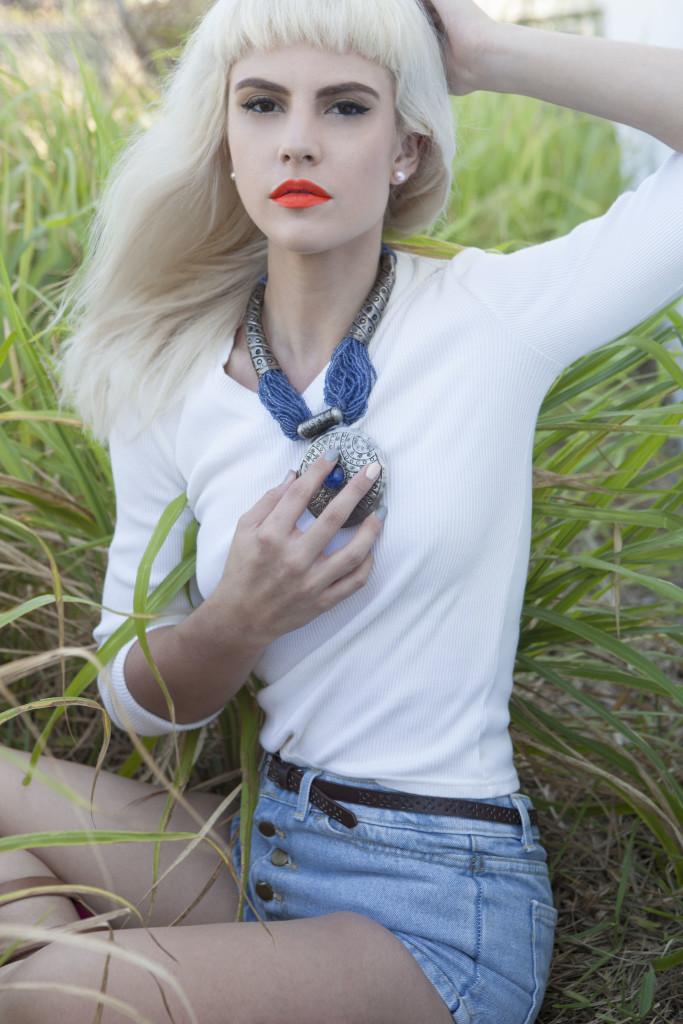 Blonde model with orange lipstick and blue jewelry sits in tall grasses.