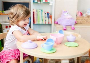 copil care se joaca cu un set de ceai - jucarii creative pentru care copilul tau iti va fi recunoscator