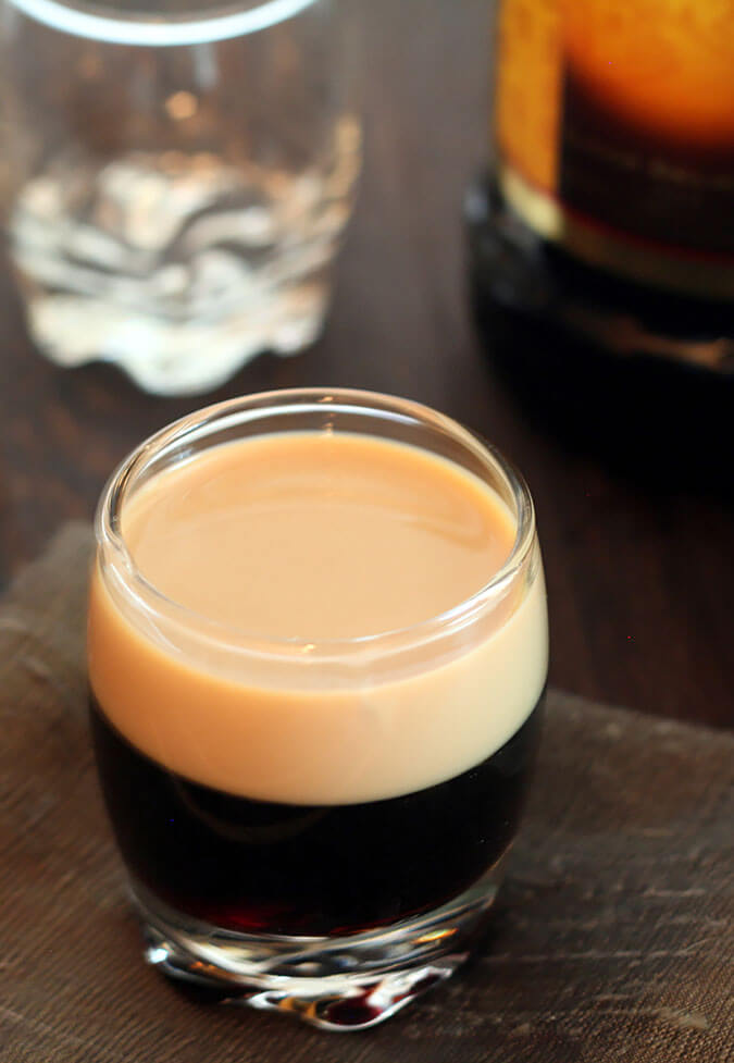 Small glass with a Baby Guinness Cocktail layering Kahlua with Baileys Irish Cream liqueurs.